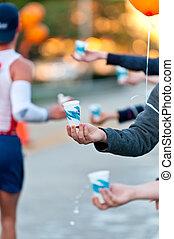 Water during a Marathon - Volunteers hands offering water...