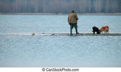 Fisherman - Man fishing with two dogs