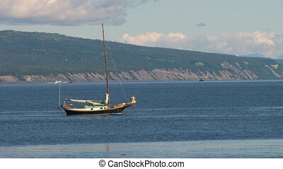 Sailboat offshore at anchor - Man rowing dinghy from...