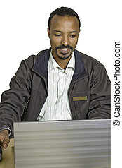 Young happy and diverse man sits at desk using laptop -...