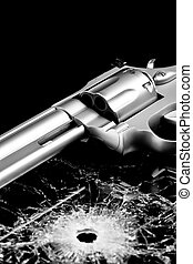 gun with bullet hole in glass - handgun with bullet hole in...