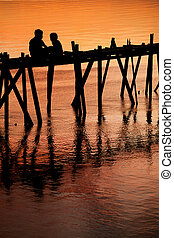 Children on bridge sunset silhouette - Silhouette of two...