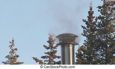 Smoking Chimney close - A stovepipe chimney exhausts wood...
