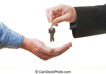 Passing keys - Hand of businessman passing a set of keys to...