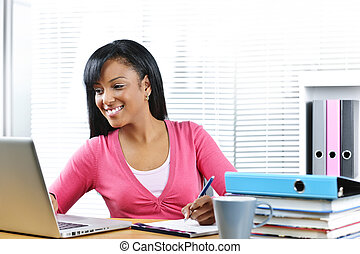 Female student studying - Smiling young black female student...