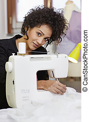 Fashion designer with sewing machine - Young hispanic female...