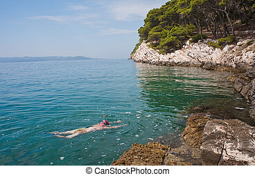 Woman with snorkelling and swimming in the sea