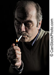 Studio portrait of a man lighting cigarette - Studio...
