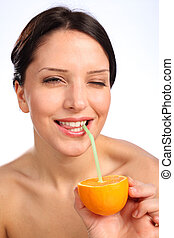 Beautiful young woman drinking juice from orange