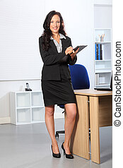Beautiful business woman standing with clipboard