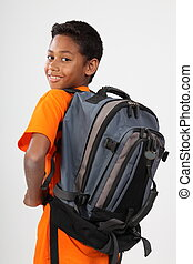 Happy ethnic schoolboy with bag