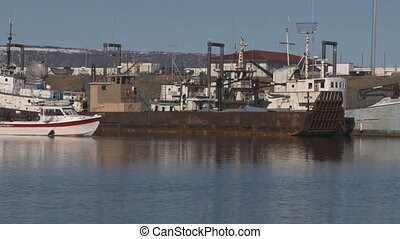 White Boat Pass by Rusted Barge - Small fishing boat with an...