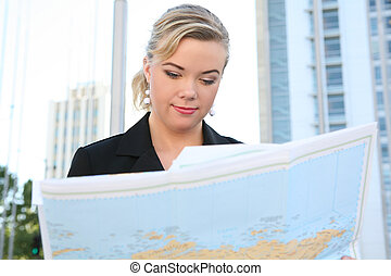 Business Woman Reading Map - A pretty blonde business woman...