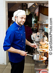 chef with scoop - professional chef cooking in commercial...