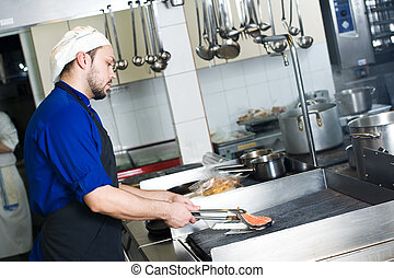 chef frying a fish on grill