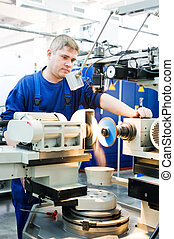 worker at machine tool operating - worker in uniform working...