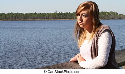 Sad Lonely Teen By Lake - Sad lonely teen looks out over a...
