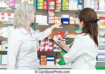 Pharmacy chemist women in drugstore - two pharmacist chemist...