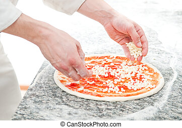 Pizza preparartion - Closeup hand of chef baker in white...