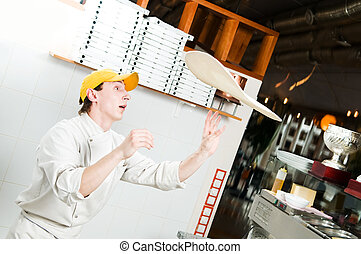 Pizza baker juggling with dough