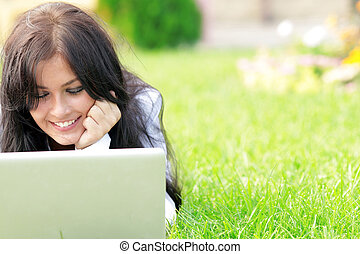 Young beautiful smiling woman using laptop on campus/home...