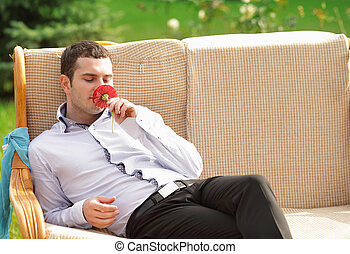 Young businessman with flower resting outdoors in sunny day....