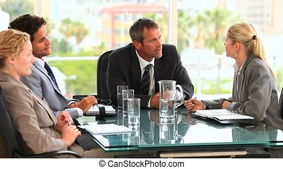 A meeting between four business people at an office