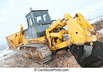 bulldozer loader at winter frozen soil excavation works -...