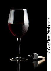 Glass of red wine and car keys on a table or bar.