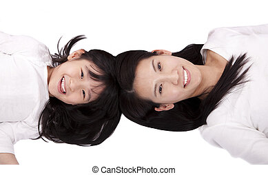 Beautiful mother and daughter lying on the white background