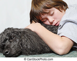 twelve year old boy asleep on standard poodle dog