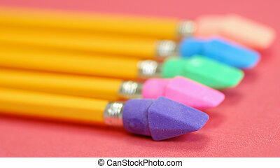 pencils with bright colored eraser ends on red background
