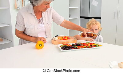 Grandmother cooking with her grandson