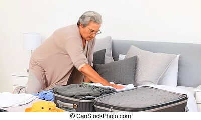 Mature woman preparing her luggages