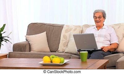 Mature woman laughing in front of her laptop