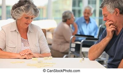 Elderly couple playing dominos