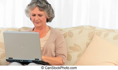 Radiant retired woman looking at her laptop