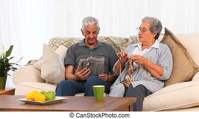 Woman knitting while her husband is reading