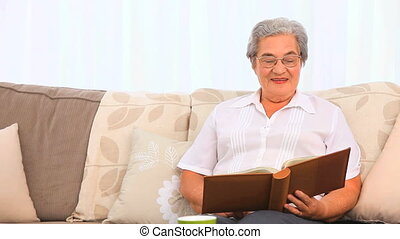 Retired woman looking at her photo album