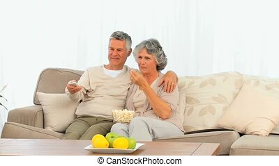 Mature couple eating popcorn in front of the tv