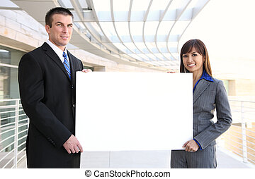 Business Team Holding Sign - An attractive man and woman...
