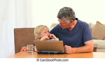 Grandfather with his grandson looking at the laptop
