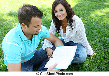 Couple Studying on Grass - Attractive Couple studying on the...
