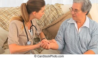 Nurse taking the pulse of her patient at home
