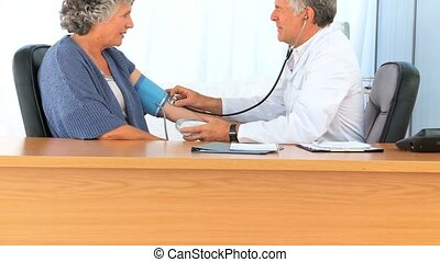 Doctor taking the blood pressure of his retired patient