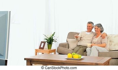 Senior couple eating popcorn in front of the tv
