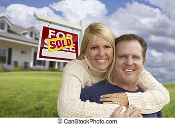 Happy Couple Hugging in Front of Sold Sign and House
