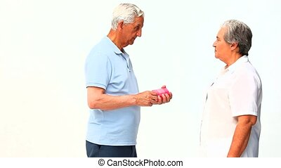 Senior man offering a present to his wife