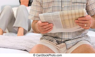 Mature man reading the newspaper wh