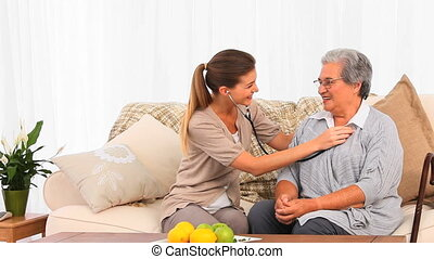 Lovely nurse taking the heartbeat of her senior patient